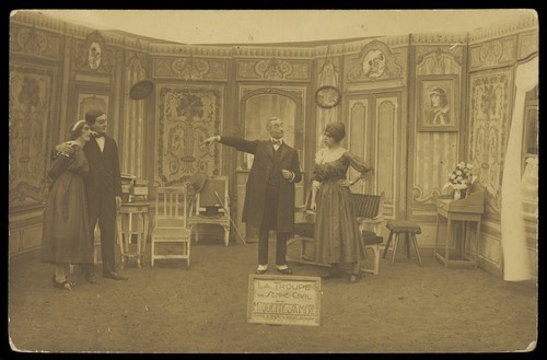 "Download the full-sized image of Amateur actors, some in drag, posing on stage for ""Miquette & sa mere""; at Sennelager prisoner of war camp in Germany. Photographic postcard, 191-."