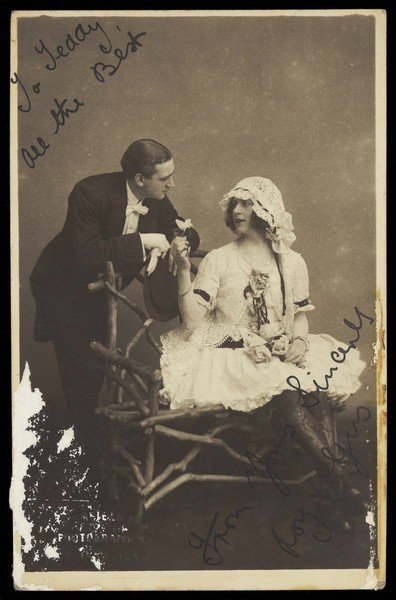 Download the full-sized image of Roy and Gus, two music-hall actors, one in drag, converse across a bench. Photographic postcard by Greenfield Bros, 192-.