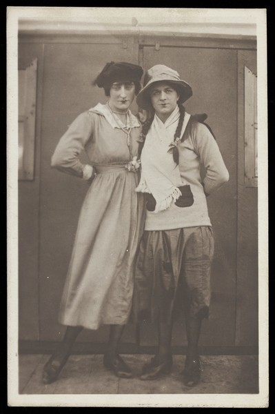 Download the full-sized image of Two men, both in drag, pose wearing hats and make-up. Photographic postcard, ca. 1918.