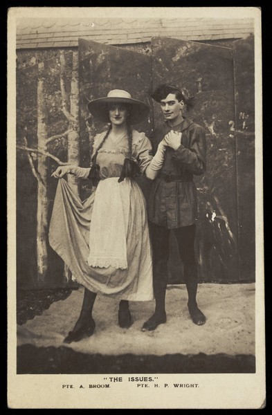 Download the full-sized image of Two members of a military concert party pose on stage: one is in drag with a large hat and pigtails. Photographic postcard, 1915-1916.