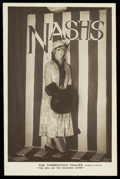 "Download the full-sized image of An soldier in drag modelling for ""The Timbertown Follies"" at a prisoner of war camp in Groningen. Photographic postcard, 191-."