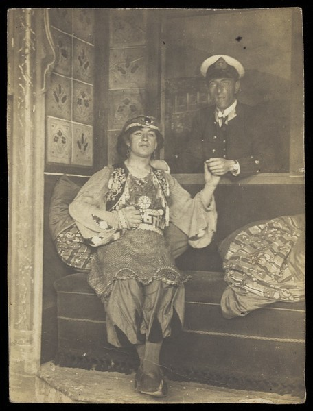 Download the full-sized image of A sailor holds hands with a man in elaborate drag. Photographic postcard, 191-.