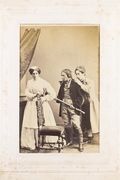 Download the full-sized image of Three men, one in drag, acting out a scene. Photograph, 189-.