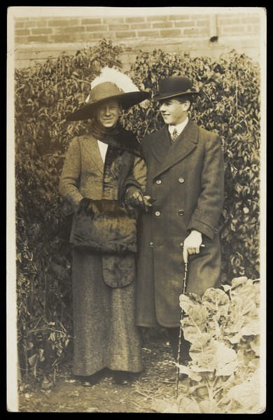 Download the full-sized image of Two men, one in drag, wearing smart attire, pose as a couple within foliage. Photographic postcard, ca. 1900.