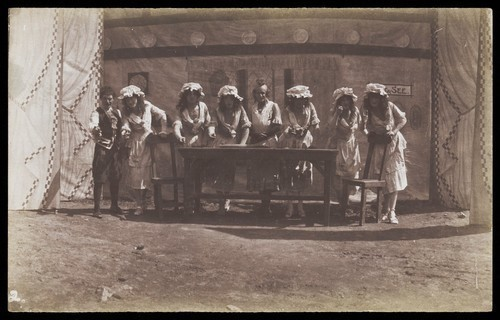 Download the full-sized image of British servicemen in drag acting out a cooking class. Photograph, 191-.