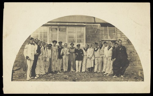 Download the full-sized image of Sailors with men in drag outside a building. Photographic postcard, 191-.