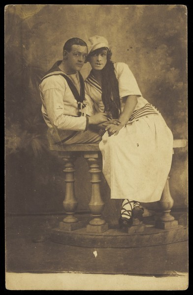 Download the full-sized image of Two sailors, one in drag, embracing while sitting on a stage balcony. Photographic postcard, 191-.