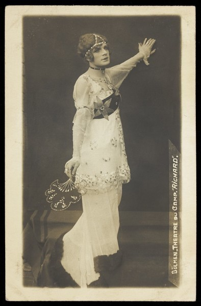Download the full-sized image of A French prisoner of war acting in an internment camp in Dülmen, performing in drag, wearing a long white dress. Photographic postcard, 191-.