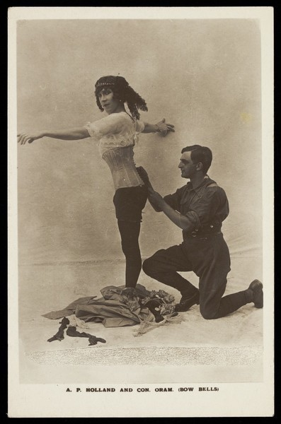 Download the full-sized image of Con Oram laces A.P. Holland (in drag) into a boned corset in a show for the Bow bells concert party. Photographic postcard, 191-.
