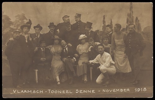 Download the full-sized image of Belgian prisoners of war, some in drag, pose on stage for a group portrait; at Sennelager prisoner of war camp in Germany. Photographic postcard, 1918.