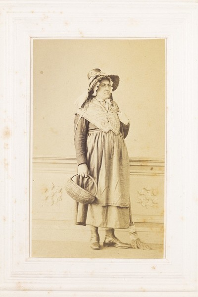 Download the full-sized image of A man in drag poses with a bonnet, basket and broom. Photograph, 189-.