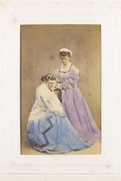 Download the full-sized image of Two men in drag posing in the act of dressing. Photograph, 189-.
