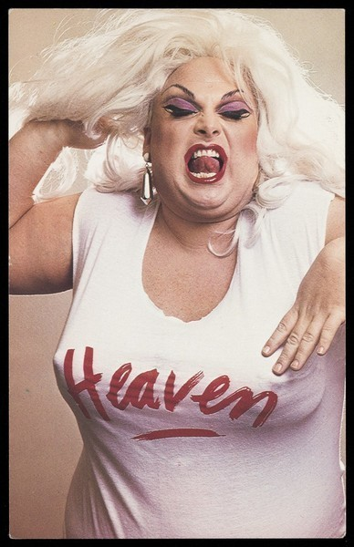 "Download the full-sized image of ""Divine"" in character, wearing a ""Heaven"" t-shirt. Colour photographic postcard, 198-."