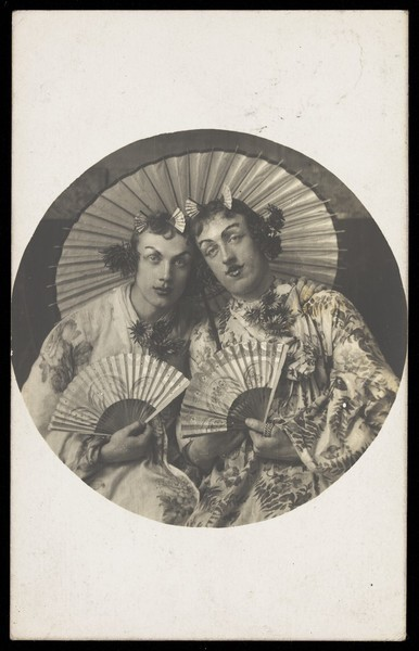 Download the full-sized image of Two young men in drag wearing Japanese costumes, pose together holding fans, underneath a parasol. Photographic postcard, 1905.