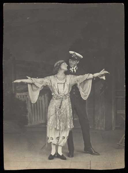 Download the full-sized image of A couple, one in drag, pose together on stage. Photographic postcard, 191-.