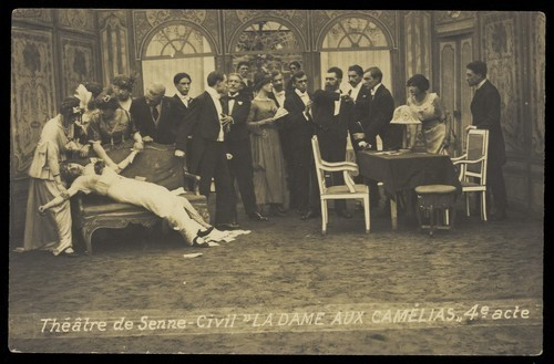 "Download the full-sized image of French or Belgian prisoners of war, some in drag, posing on stage during a crowded scene of ""La dame aux camélias""; at Sennelager prisoner of war camp in Germany. Photographic postcard, 191-."