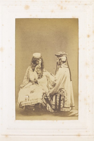 Download the full-sized image of Two men in drag (?) sitting opposite each other. Photograph, 189-.